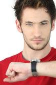 Портрет молодого человека, его часы-консалтинг — Стоковое фото