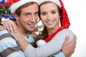 Festive couple hugging by the Christmas tree — Stock Photo