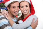 Slavnostní pár objímání vánoční stromeček — Stock fotografie