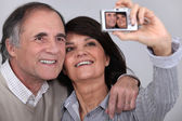 Middle aged couple taking a picture of themselves — Stock Photo