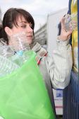 Brunette recycling plastic bottles — Stock Photo