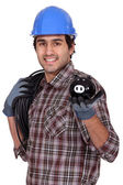 Electrician holding piggy-bank — Stock Photo