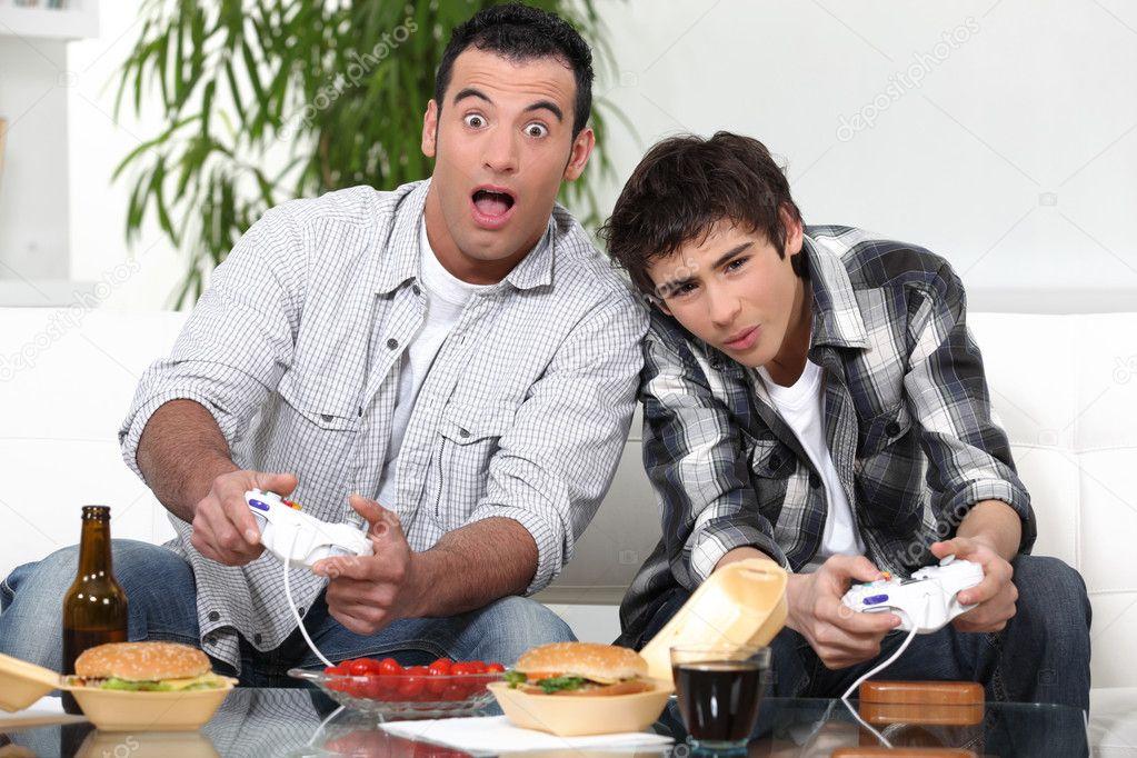 Pai e filho tendo ers 227 o jogando videogame foto stock