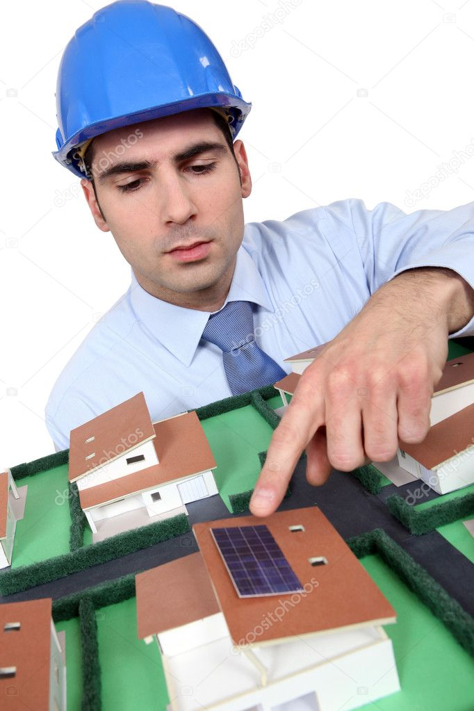 Architect pointing to solar panel on model house — Stock Photo #11055120