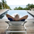 Senior man relaxing poolside - Stock Photo