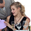 Stock Photo: Boyfriend surprising girlfriend with heart-shaped box