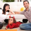 Parents with children dressed as devil - Stock Photo