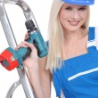 Stock Photo: Blonde handywomwearing overall and posing with drill and stepladder