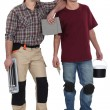 Two men about to plaster and tile house - Stock Photo