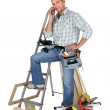 Stock Photo: Carpenter stood by equipment making call
