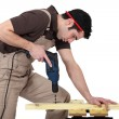 Stock Photo: Man drilling hole in wood