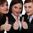 Three businesswomen giving the thumb up. — Стоковая фотография