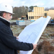 Photo: Construction worker examining blueprint