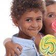 Two young children eating lollipops — Stock Photo