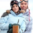 Couple stood in front of skiing holiday accommodation — Stock Photo #11065048