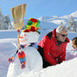 Father and daughter with snowman — Stock Photo #11065154