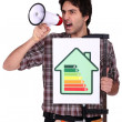 Man with speaker and energy rating sign — Stock Photo