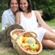 Stock Photo: Couple sitting in the grass with fruit basket