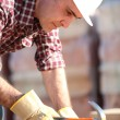Builder using a hammer - Stock Photo