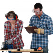 Foto Stock: Craftswoman and craftsman working together in their workshop