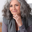 Grey-haired woman touching chin - Stock Photo