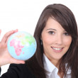 Young smart woman holding the world in her hand — Stock Photo