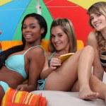 Friends under a beach umbrella — Stock Photo #11068604