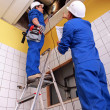 Stock Photo: Man and woman repairing ventilation system