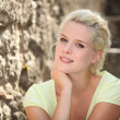 Blonde woman next to stone wall - Lizenzfreies Foto