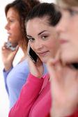 Three women using their mobile telephones — Stock Photo