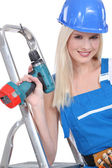 A blonde handywoman wearing an overall and posing with a drill and a stepladder — Stock Photo