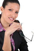 Brunet woman holding reading glasses — Stock Photo