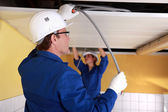 Craftsman and craftswoman working on the electric installation — Stock Photo