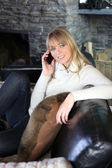 Blond on comfortable couch gossiping over the telephone — Stock Photo
