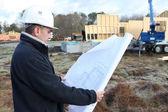 Construction worker examining a blueprint — Stock Photo