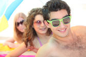 Youth on the beach wearing sunglasses — Stock Photo
