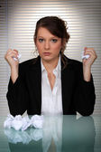 Angry woman scrunching up paper into balls — Stock Photo