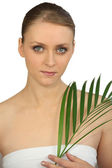 Woman holding a fern — Stock Photo