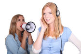 Girl listening to music and friend shouting in loudspeaker — Stock Photo