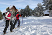 Couple skiing by chalets — Stock Photo