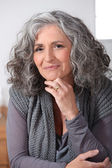 Grey-haired woman touching chin — Stock Photo