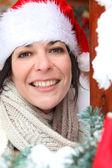 женщина, отвечая на дверь в праздничной шляпа — Стоковое фото
