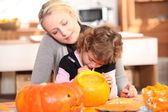 Mom and daughter carving a pumpkin — Stock Photo