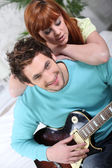 Man impressing girl by playing the guitar — Stock Photo
