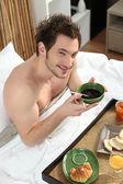 Homem tomando café da manhã na cama — Fotografia Stock