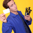 Stock Photo: Handymshowing his business card
