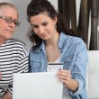 Stock Photo: Homecare helping senior womin making online shopping