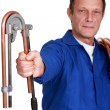 Plumber using tool to bend copper pipe - Stock Photo