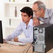 Stock Photo: Grandfather and grandson looking at the computer
