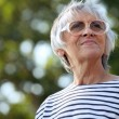 Senior woman walking in the park — Stock Photo